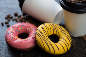 Close-up of yellow and pink donuts with takeaway coffee cups in the background, selective focus