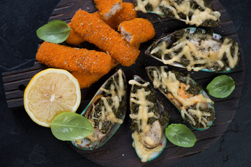 Above view of mussels baked with spinach and cheese and roasted fish fingers on a wooden serving board, closeup