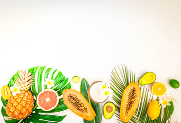 fresh exotic fruits with green tropical leves flat lay top view border, summer diet background, retro toned