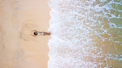 Aerial view of young sporty lady in blue sexy bikini. Hot beach with cool waves. Summer and holiday concept, seascape with girl, beach, beautiful waves, blue water. Top view from drone shot.