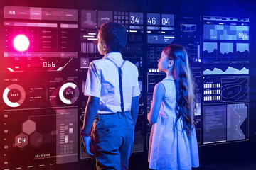 Two modern kids. Calm clever boy and girl standing in front of a large futuristic device and looking at the transparent screen of it while being interested in the construction of a security system