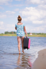Girl walking on water with a suitcase