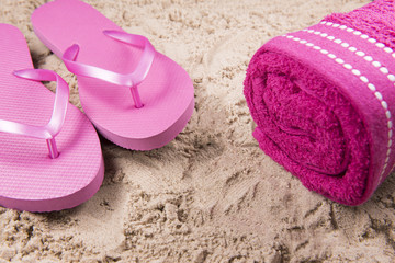 Beach background image of pink flip flops and a beach towel on a sandy beach