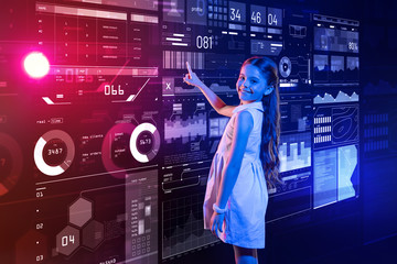 Confident child. Cute positive girl smiling and looking happy while standing next to the futuristic device and pointing to the screen of it