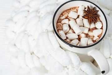 White cup of hot chocolate with marshmallows on pompon yarn. Pleasant moments.  Selective focus.