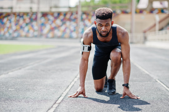 African american male athlete in sportswear racing alone down a running track at stadium.