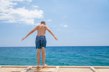 Teenage boy in swimming shorts standing at the edge of on the wooden jetty pier in front of the sea on the beach, balancing ready to jump into water.