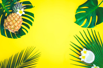 Summer flat lay frame with fresh tropical green leaves, coco and pineapples frame on yellow, retro toned