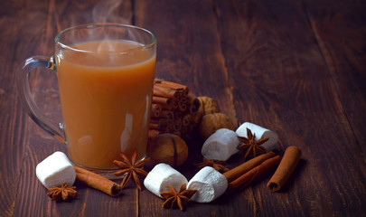 Hot coffee, sweets and spices on an old wooden table. Christmas atmosphere. Comfort. Winter.