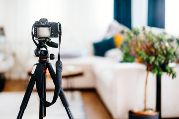 Camera on a tripod taking photographs of interior design, furniture and houses