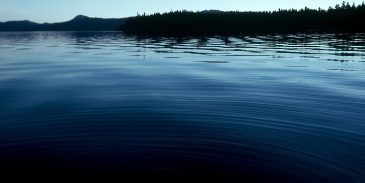 Priest Lake smooth water blue sky reflected