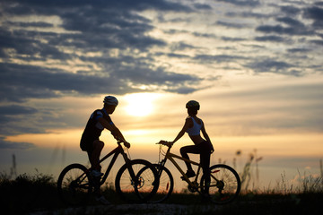 Man and woman cyclists on bicycles standing on the road among the field grass opposite each other and looking to the side at sunset. A magical sky with clouds among which the sun that sits is seen