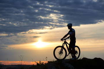 Athletic man in sportswear and helmet holding hands on bicycle and standing near it. Energetic cyclist posing in twilight and sunset on hill and against wonderful background of sky and clouds.