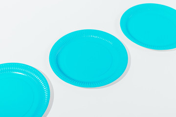 Three blue disposable plates of on white table