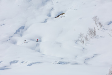 two tourists on the snowed sidehill of mountain. Alps, France, Bessans.