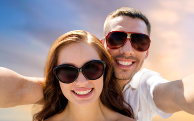 love, summer and people concept - smiling couple wearing sunglasses making selfie over evening sky background