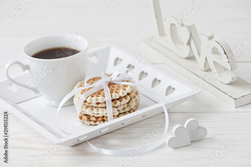 Fresh homemade waffles and  cup of coffee on a white tray, Love Letters and two heart shapes. Close-up on  white vintage wooden background. Concept for the Valentine's Day, Mother's Day