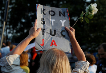 A woman holds poster which reads 'Constitution' during an anti-government protest in support of free courts in front of the Parliament building in Warsaw