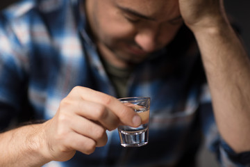 alcoholism, alcohol addiction and people concept - close up of male alcoholic drinking vodka shot at night