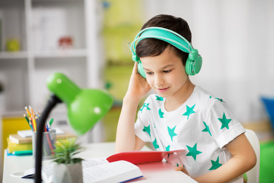 education, childhood and school concept - student boy in headphones reading book at home