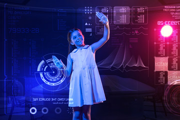 Happy girl. Cheerful emotional girl wearing a lovely dress and smiling while putting her hands on the screen of a futuristic device