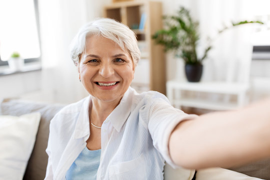 technology, communication and people concept - happy smiling senior woman in glasses taking selfie at home