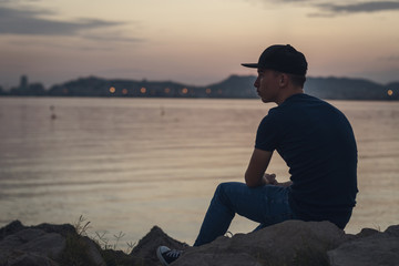 Pensive teen with black cap sitting on the rocks and looking to the sea Wall mural