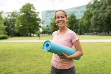 fitness, sport and healthy lifestyle concept - happy smiling woman with exercise mat at park