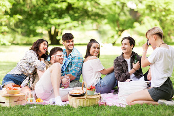 friendship, leisure and technology concept - group of happy smiling friends with non alcoholic drinks photographing at picnic in summer park