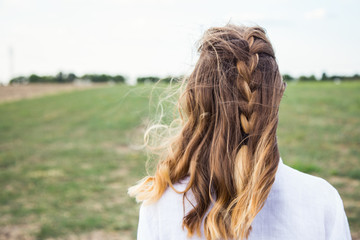 Portrait of young blonde from behind with carelessly braided pigtail and flying hair in wind in field.
