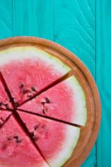 Fresh sliced watermelon on wooden round desk on mint green background.