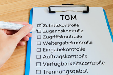 Plate with the inscription TOM (Technisch organisatorische Maßnahmen)  in English Technically organizational measures with a tablet and block to signal typical activities of data protection officers