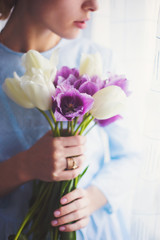 Young tender girl holding beautiful spring bouquet of purple and white tulips