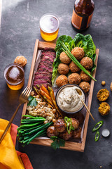 Middle eastern or arabic dishes and assorted meze on a dark background. Meat, falafel, baba ghanoush, vegetables. Halal food. Space for text. Top view.