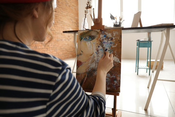 Female artist painting in workshop