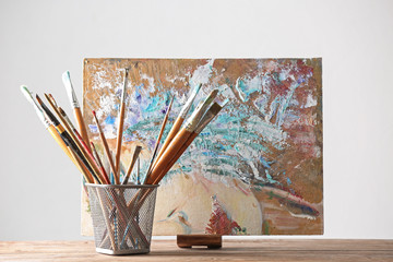 Holder with paint brushes and picture on wooden table against light background