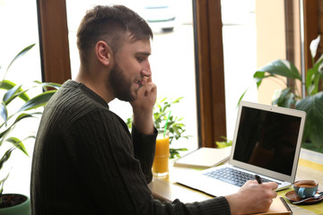 Young freelancer talking on mobile phone while working on laptop in cafe