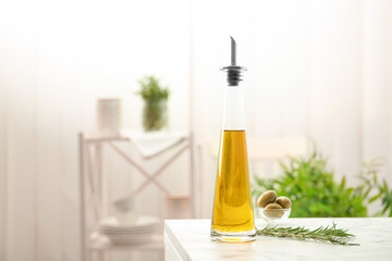 Bottle with fresh rosemary oil on table