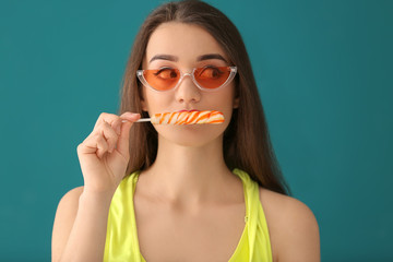 Attractive young woman with lollipop on color background