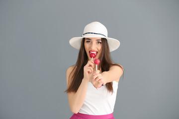 Attractive young woman with lollipops on color background