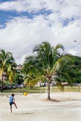 Enfant jouant au football sous les tropiques