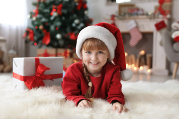 Cute little child in Santa hat with Christmas gift box at home