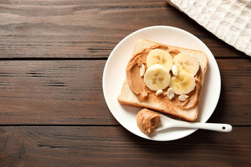 Toast bread with peanut butter and banana slices on wooden table