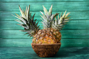 Wicker basket with delicious pineapples on table against wooden background