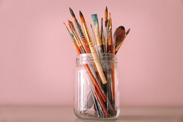 Glass jar with set of brushes on table against color background