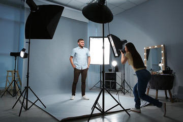 Handsome model posing for professional photographer in photo studio