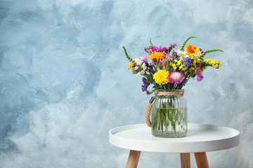 Vase with wild flowers on table against color background