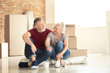 Mature couple with moving boxes sitting on carpet at new home