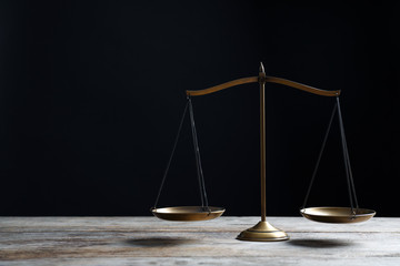Scales of justice on wooden table against dark background. Law concept