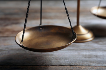 Scales of justice on wooden table, closeup. Law concept